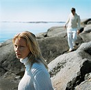 Two young people walking on rocky coast
