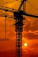 at a construction place, a crane with the glow of the setting sun