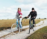 Two people riding bikes on dirt road