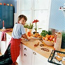 Boy helping with making biscuits in domestic kitchen