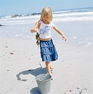 Girl picking up lobsters on sandy beach