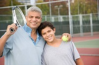 Hispanic father and son on tennis court