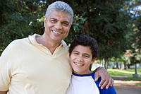 Hispanic father with arm around son