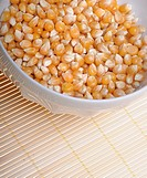 Corn seeds in small bowl on bamboo mat