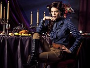 Artistic high fashion photo of a beautiful woman sitting at a table with remains of a festive dinner