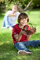 Germany, Boy 10_11 Years holding easter eggs with man in background