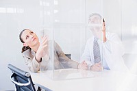 Business people looking at transparent cube in conference room