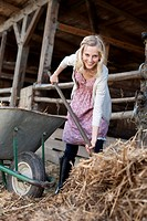 Germany, Saxony, Young woman working in the farm