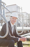 Businessman in hard_hat sitting on industrial steps