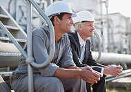 Businessman and worker in hard_hats sitting on industrial steps