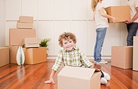 Boy sitting with box on the floor of his new house