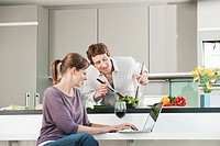 Germany, Hamburg, Man preparing salad with woman using laptop in kitchen