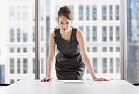 Businesswoman leaning on desk in office