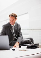 Businessman drinking coffee and typing on laptop