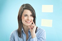 Businesswoman looking at adhesive notes, smiling