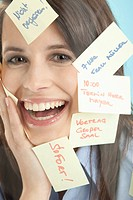Businesswoman with adhesive notes, smiling (thumbnail)