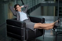 Germany, Bavaria, Business woman resting on chair, smiling, portrait