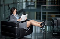 Germany, Bavaria, Business woman reading newspaper
