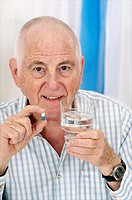 Senior man holding a pill in one hand and a glass of water in hte other about to take his medical treatment