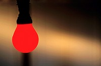 Illuminated red lightbulb