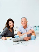 Mature couple having breakfast, reading newspaper