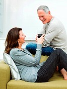 Mature couple sitting on sofa with wine