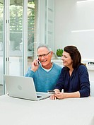 Mature couple using laptop with credit card