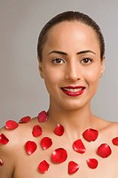 Portrait of a woman smiling with rose petals on her body