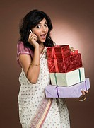 Woman talking on a mobile phone and holding gifts