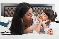 Woman smiling with her daughter on the bed