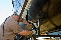 Ethanol plant technician attaching anti-tampering seal to rail car filled with ethanol before shipment, Richardton, North Dakota