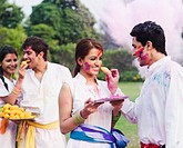 Two couples celebrating Holi