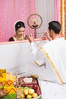 Bridegroom putting Mangal Sutra to a bride at the South Indian wedding ceremony