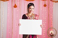 Portrait of a bride in traditional South Indian dress holding a placard and smiling