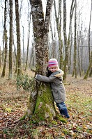 Five year old girl hugging a tree