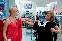 Young women shopping and comparing different clothes in store