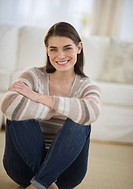 Portrait of attractive young woman sitting on floor