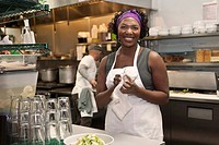 Black waitress working in restaurant kitchen