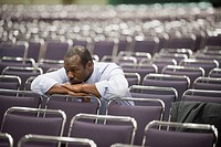 Impatient Black businessman waiting in empty conference center