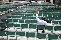 Black businessman waiting in empty conference center waving