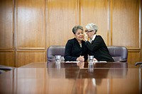 Businesswomen whispering together in conference room