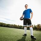 Caucasian soccer player holding ball on soccer field