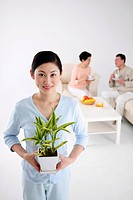 Woman holding potted plant, senior man and senior woman chatting in the background