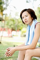 Woman sitting on the bench with towel around the neck