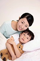 Woman with girl lying on bed smiling