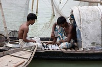 Fishermen play chess on the boat in their leisure time Manikgonj, Bangladesh September 2008