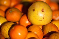 Orange with a smiley face on it at a market stall