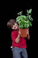 Portrait of a boy holding a potted plant