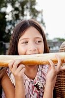 Girl biting a loaf of bread