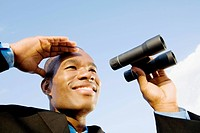 Close_up of a businessman holding binoculars and smiling